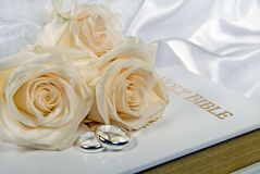 Wedding rings and roses on Bible Royalty Free Stock Photos