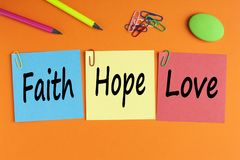 Faith Hope and Love Concept. FAITH, HOPE and LOVE written on color notes with and office supplies. Business Concept. Top view royalty free stock photo