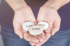 Faith, Hope and Love. Three stones with the words Faith, Hope, Love in the woman's palms Royalty Free Stock Images