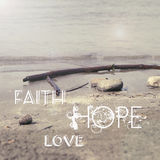 Faith Hope Love. Words on sand stock photos