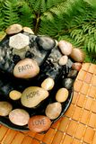 Faith Hope Love Zen Inspired Fountain. A zen-like waterfall fountain with faith, hope, and love engraved stones. Displayed on a bamboo placemat with green ferns Royalty Free Stock Photo
