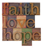 Faith, love and hope. Biblical, spiritual  or metaphysical reminder - faith, hope and love in old wooden letterpress type blocks, stained by colorful inks Royalty Free Stock Image