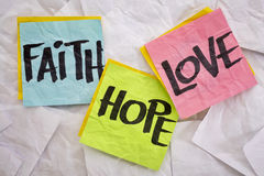 Faith, love and hope. Colorful sticky notes on a background of crumpled white notes Stock Photography