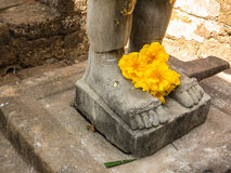The Faith. People lay down the yellow flower on the Buddha statue Stock Photography