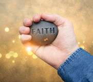 Faith stone in hand royalty free stock photography