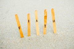 Faith. Text on wooden  word faith on the sand beach Stock Photos