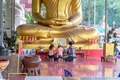 The faith. THAMAI, CHANTHABURI, THAILAND - JULY 31 : Unidentified family is worshiping the big buddha image on July 31, 2015 at Wat Khaosukim, Thamai Royalty Free Stock Photo