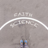 Faith vs science text on asphalt ground, feet and shoes on floor Royalty Free Stock Image