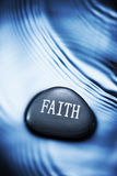 Faith Christianity Religion Background. A stone with the word faith on it with water and ripples stock images