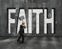 Faith word on concrete wall with man holding hammer Royalty Free Stock Images
