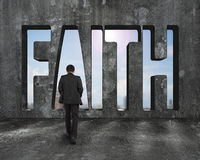 Faith word on concrete wall with man walking toward Royalty Free Stock Photos