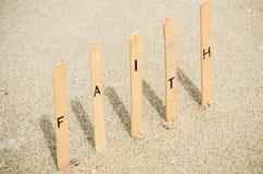 Faith. Word faith pin on the sand beach Stock Photos
