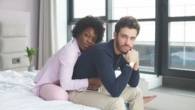 Faithful, affectionate african woman is sitting behind and hugging tenderly her handsome husband. They looking at camera while sit on the bed in spacious room stock footage