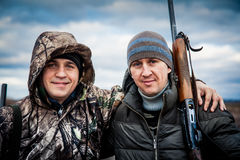 Faithful cheerful friends standing together in front of dramatic sky in overcast day during hunting season embracing each over Royalty Free Stock Photo