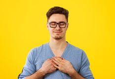 Faithful man with eyes closed keeps hands on chest near heart, shows kindness royalty free stock photos