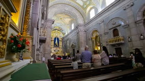 Faithful praying in the interior of the Sanctuary of Sao Bento da Porta Aberta stock footage