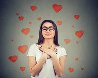 Faithful woman with eyes closed keeps hands on chest near heart royalty free stock photos