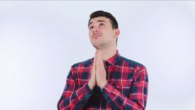 Prayer gesture. Faithfull young man wearing plaid red shirt holding palms together as prayer gesture isolated over white background. Guy having troubles and stock video