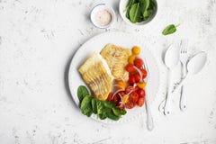 Faixa branca fritada dos bacalhaus do mar fresco com salada de tomates de cereja e de cebolas vermelhas doces Conceito do aliment imagens de stock