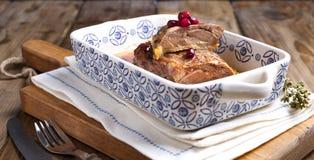 Faixa cozida do pato com bagas da romã em uma bandeja de cozimento cerâmica com testes padrões em uma tabela de madeira Alimento  fotos de stock royalty free