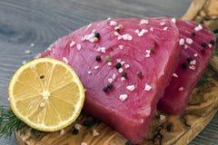 Faixa crua do atum com aneto, limão e pimentas na placa de corte verde-oliva imagem de stock