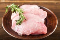 Faixa da galinha com alecrins em uma placa de madeira em uma tabela estrutural Carne do peru e grãos de pimenta close-up e espaço fotografia de stock royalty free