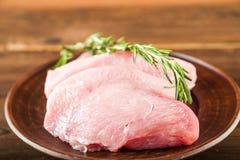 Faixa da galinha com alecrins em uma placa de madeira em uma tabela estrutural Carne do peru e grãos de pimenta close-up e espaço foto de stock