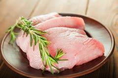 Faixa da galinha com alecrins em uma placa de madeira em uma tabela estrutural Carne do peru e grãos de pimenta close-up e espaço imagem de stock royalty free