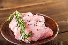 Faixa da galinha com alecrins em uma placa de madeira em uma tabela estrutural Carne do peru e grãos de pimenta close-up e espaço imagens de stock