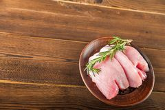 Faixa da galinha com alecrins em uma placa de madeira em uma tabela estrutural Carne do peru e grãos de pimenta close-up e espaço fotos de stock royalty free