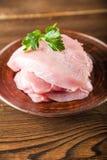Faixa da galinha com um ramo da salsa em uma placa de madeira em uma tabela estrutural Fim cru da carne do peru acima e espaço da foto de stock royalty free
