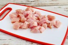 A faixa da galinha cortou nos cubos em uma placa de corte branca ponto por ponto cozinhando Imagens de Stock