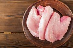 Faixa da galinha em uma placa de madeira em uma tabela estrutural Fim cru da carne do peru acima e espaço da cópia imagem de stock