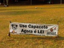 Faixa da informação sobre o uso imperativo do capacete para skateres no parque da independência em Sao Paulo fotografia de stock royalty free
