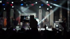 A faixa da música de Smartphone Live Concert Performance Taking Photo da câmara de vídeo do registro da terra arrendada da mão mo filme