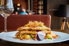 Faixa de bacalhau cozida com os vegetais no interior do restaurante Imagens de Stock Royalty Free