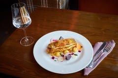 Faixa de bacalhau cozida com os vegetais no interior do restaurante Imagem de Stock Royalty Free