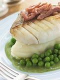 Faixa de bacalhau Roasted com as ervilhas e o bacon da batata de erva-benta Foto de Stock Royalty Free