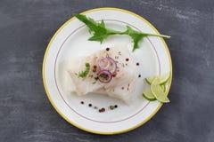 Faixa de peixes crua fresca do bacalhau em uma placa com salsa e limão no fundo cinzento da ardósia fotos de stock