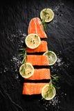 A faixa de peixes crus fresca cortou em parcelas com fatias, alecrins, sal e pimenta do limão no fundo de pedra preto Imagem de Stock Royalty Free