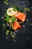 A faixa de peixes crus fresca cortou em parcelas com fatias, alecrins, salsa, sal e pimenta do limão no fundo de pedra preto Foto de Stock Royalty Free