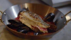 Faixa de peixes que encontra-se na bandeja de alumínio profunda com os punhos com interior vermelho do molho com os mexilhões que vídeos de arquivo