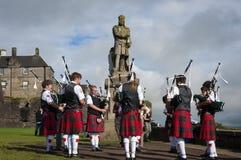 Faixa dos gaiteiros que jogam na frente da estátua de Robert o Bruce em Stirling Castle em Stirling, Escócia imagens de stock royalty free