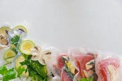 A faixa e os vagatables em sacos de vácuo para o vide sous que coocing no branco marbleized o fundo Fotografia de Stock