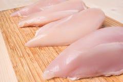 Faixa fresca da galinha em uma placa de corte de bambu Fotos de Stock