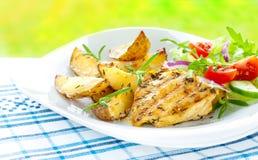 Faixa grelhada do peito de frango com batatas e salada Fotos de Stock Royalty Free