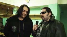 A faixa Kukryniksy Alex Gorshenev do solista dá a entrevista em de bastidores ao homem do balancim no casaco de cabedal vídeos de arquivo