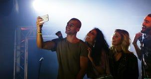 Faixa musical que toma o selfie com telefone celular em um concerto 4k vídeos de arquivo