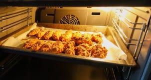 Faixa recentemente cozida da galinha em uma folha de cozimento em um forno elétrico Cozinhando pepitas de galinha série imagem de stock royalty free