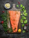 Faixa salmon perfeita na placa de corte rústica com os ingredientes frescos para o cozimento saboroso imagens de stock royalty free